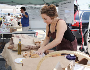 Kelsey Nichols of Wave Hill Breads prepares fresh slices of bread for customers.